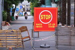 An alley is blocked with chairs and wood planks in Vung Tau, Vietnam, Monday, Sept. 13, 2021. In Vung Tau, just outside Ho Chi Minh city, streets are sealed and checkpoints are set up to control the movement of people. Barbed wire, door panels, steel sheets, chairs and tables are among materials being used to fence up alleys and isolate neighborhoods. (AP Photo/Hau Dinh)