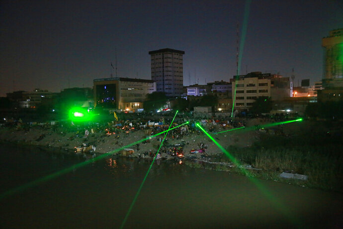 Anti-government protesters shoot laser lights at security forces during clashes on a bridge leading to the Green Zone government areas during ongoing protests in Baghdad, Iraq, Wednesday, Nov. 6, 2019. Tens of thousands of people have taken to the streets in recent weeks in the capital, Baghdad, and across the Shiite south, demanding sweeping political change. (AP Photo/Khalid Mohammed)