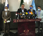 Head of Atomic Energy Organization of Iran, Mohammad Eslami, center, speaks during a joint press briefing with Director General of International Atomic Energy Agency, IAEA, Rafael Mariano Grossi, second right, in Tehran, Iran, Sunday, Sept. 12, 2021. Iran agreed Sunday to allow international inspectors to install new memory cards into surveillance cameras at its sensitive nuclear sites and to continue filming there, averting a diplomatic showdown this week. (Atomic Energy Organization of Iran via AP)