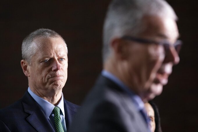 Massachusetts Gov. Charlie Baker, left, listens as CEO of the Boston Athletic Association Thomas Grilk talks about the postponement of the Boston Marathon during a news conference, Friday, March, 13, 2020, in Boston. The Marathon, which was due to be run on April 20 will be run on Monday, Sept. 14, 2020, due to concerns about the coronavirus. For most people, the new coronavirus causes only mild or moderate symptoms, such as fever and cough. For some, especially older adults and people with existing health problems, it can cause more severe illness, including pneumonia. The vast majority of people recover from the new virus. (AP Photo/Michael Dwyer)