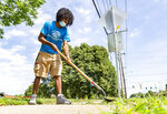 CORRECTS STATE TO ILLINOIS MacArthur senior Nigel Lawson works to clear a sidewalk during the coronavirus outbreak at Boys & Girls Clubs of Decatur, Ill., Tuesday, July 14, 2020. Students are paid using a federal grant through Workforce Investment Solutions. (Clay Jackson/Herald & Review via AP)