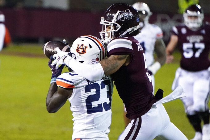Auburn defensive back Roger McCreary (23) intercepts a pass intended for Mississippi State wide receiver Osirus Mitchell (5) during the first half of an NCAA college football game Saturday, Dec. 12, 2020, in Starkville, Miss. (AP Photo/Rogelio V. Solis)