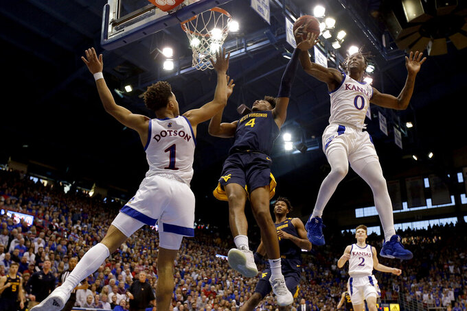 FILE - Kansas' Marcus Garrett (0) knocks the ball away from West Virginia's Miles McBride (4) during the second half of an NCAA college basketball game in Lawrence, Kansas, in this Saturday, Jan. 4, 2020, file photo. At left is Kansas' Devon Dotson (1). Garrett averaged 9.2 points last season, but his biggest contributions come on the other end of the floor. The 6-5 guard was named the Naismith national defensive player of the year last season. (AP Photo/Charlie Riedel, File)