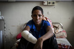 """FILE - In this Thursday, May 6, 2021 file photo, Haftom Gebretsadik, a 17-year-old from Freweini, Ethiopia, near Hawzen, who had his right hand amputated and lost fingers on his left after an artillery round struck his home in March, sits on his bed at the Ayder Referral Hospital in Mekele, in the Tigray region of northern Ethiopia. The United States said Thursday, Aug. 12, 2021 it is sending a special envoy to Ethiopia as the fast-moving conflict in the Tigray region has spread into neighboring regions and Ethiopia's government this week called on all able citizens to stop the resurgent Tigray forces """"once and for all."""" (AP Photo/Ben Curtis, File)"""