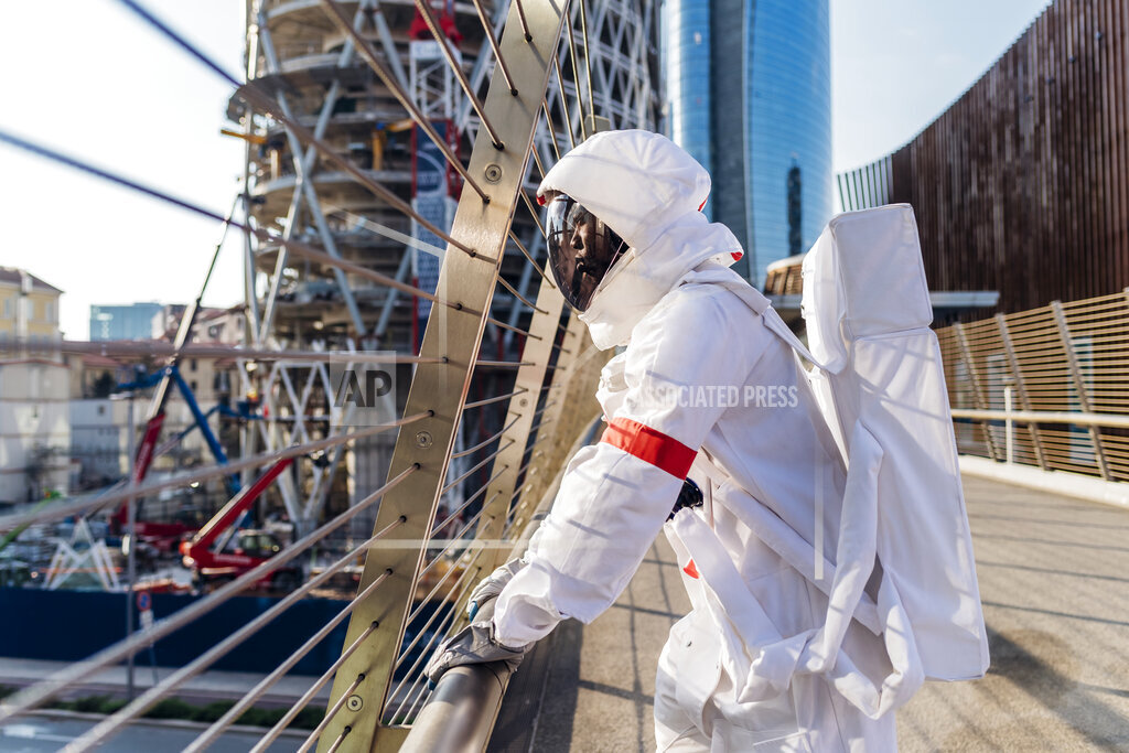 African male astronaut standing by railing on bridge