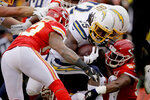 Los Angeles Chargers running back Melvin Gordon III (25) is tackled by Kansas City Chiefs linebacker Anthony Hitchens, left, and linebacker Reggie Ragland (59) during the first half of an NFL football game in Kansas City, Mo., Sunday, Dec. 29, 2019. (AP Photo/Charlie Riedel)