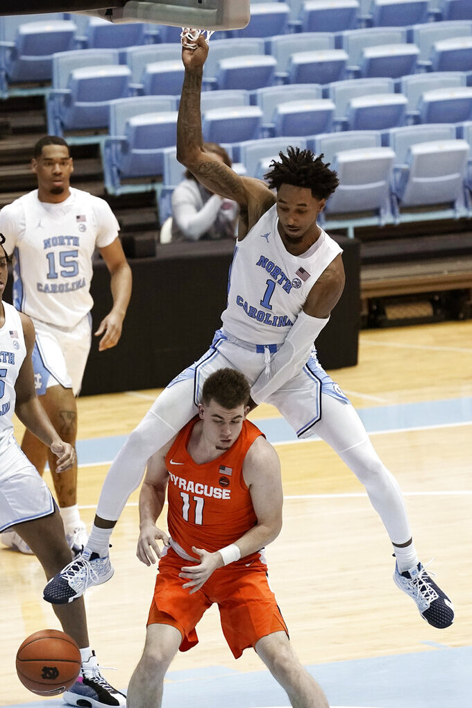 North Carolina guard Leaky Black (1) comes down over the back of Syracuse guard Joseph Girard III (11) during the second half of an NCAA college basketball game in Chapel Hill, N.C., Tuesday, Jan. 12, 2021. (AP Photo/Gerry Broome)