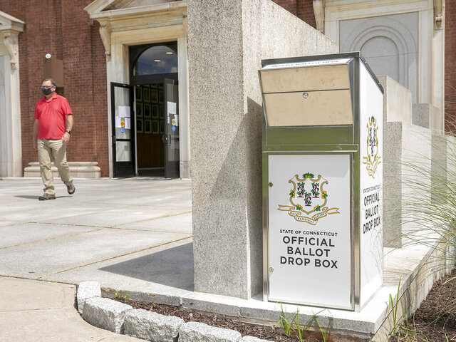 Chris Pudvah, Meriden housing inspector, walks by a new ballot drop box installed on the southside of Meriden City Hall, Tuesday, July 14, 2020, in Meriden, Conn. (Dave Zajac/Record-Journal via AP)
