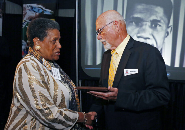 FILE - In this April 26, 2014 file photo, Myrlie Evers-Williams, widow of the murdered Mississippi civil rights leader Medgar Evers, receives the 2014 Mississippi Associated Press Broadcasters Pioneers of Television award from retired Jackson, Miss., bureau Associated Press news editor Ron Harrist in Jackson, Miss.  Harrist has died at the age of 77 of complications from leukemia. The Mississippi journalist had a four-decade career with the AP, covering Elvis Presley, black separatists, white supremacists and college football legends over the years. (AP Photo/Rogelio V. Solis, File)