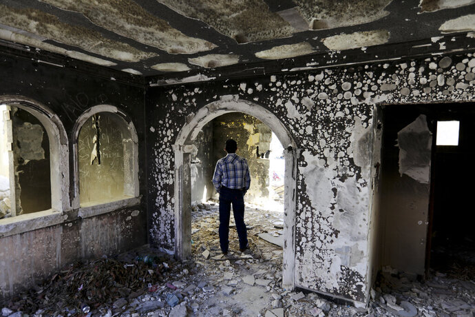 A former policeman walks through an abandoned home, torched by the Zetas cartel eight years back, in Allende, Coahuila state, Mexico, Tuesday, Dec. 3, 2019. In an act of revenge cartel members in 2011 razed and burned houses and disappeared people just by bearing the last name of the alleged traitor. Residents of the small town of Villa Union, 12 miles from Allende, said Tuesday that they fear a return to the days of 2010-2013, when the old Zetas cartel killed, burned and abducted Coahuila citizens. (AP Photo/Eduardo Verdugo)