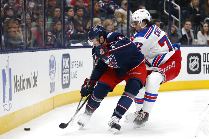 Columbus Blue Jackets' Andrew Peeke, left, tries to clear the puck away from New York Rangers' Filip Chytil, of the Czech Republic, during the first period of an NHL hockey game Friday, Feb. 14, 2020, in Columbus, Ohio. (AP Photo/Jay LaPrete)