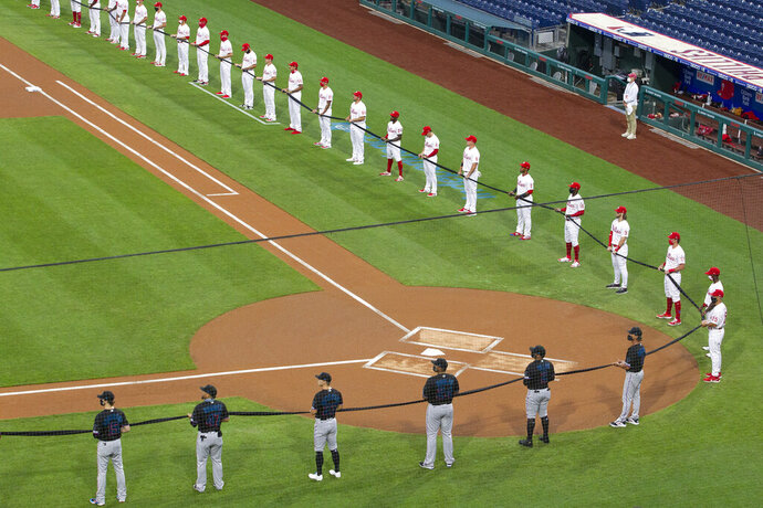 The Philadelphia Phillies, top, and the Miami Marlins hold a black ribbon in honor of the Black Lives Matter movement and in memory of George Floyd, before a baseball game Friday, July 24, 2020, in Philadelphia. Major League Baseball has already postponed a second scheduled game between Miami and Baltimore after more than a dozen Marlins players and staff tested positive for the coronavirus, prompting the club to lock down in Philadelphia. Commissioner Rob Manfred said the soonest the Marlins could resume their schedule is Wednesday, when they are set to play in Baltimore. (Charles Fox/The Philadelphia Inquirer via AP)