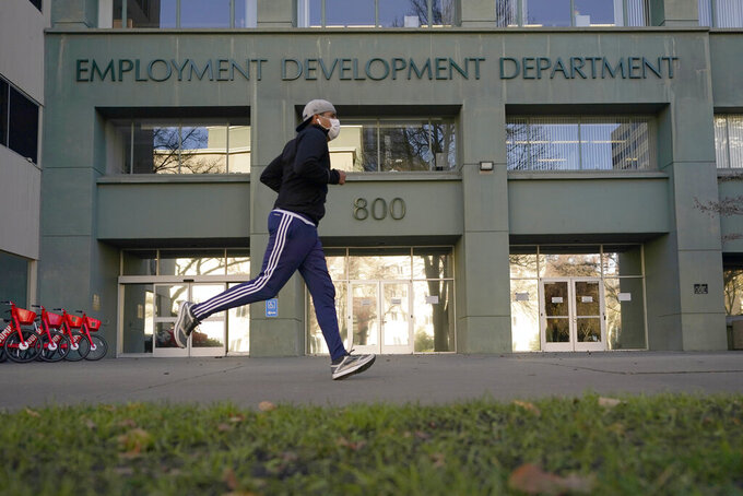 FILE - In his Dec. 18, 2020, file photo a runner passes the office of the California Employment Development Department in Sacramento, Calif. On Thursday, July 22, 2021, California Gov. Gavin Newsom's administration announced a change in how it pays unemployment benefits that is expected to help up to 100,000 people whose benefits have been suspended tor weeks or months. The change announced Thursday is the result of a settlement between the EDD and the Center for Workers' Rights. (AP Photo/Rich Pedroncelli, File)