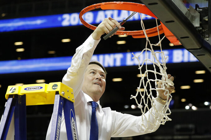 Saint Louis coach Travis Ford cuts the net after the team defeated St. Bonaventure during an NCAA college basketball game in the Atlantic 10 men's tournament final Sunday, March 17, 2019, in New York. Saint Louis won 55-53. (AP Photo/Julio Cortez)