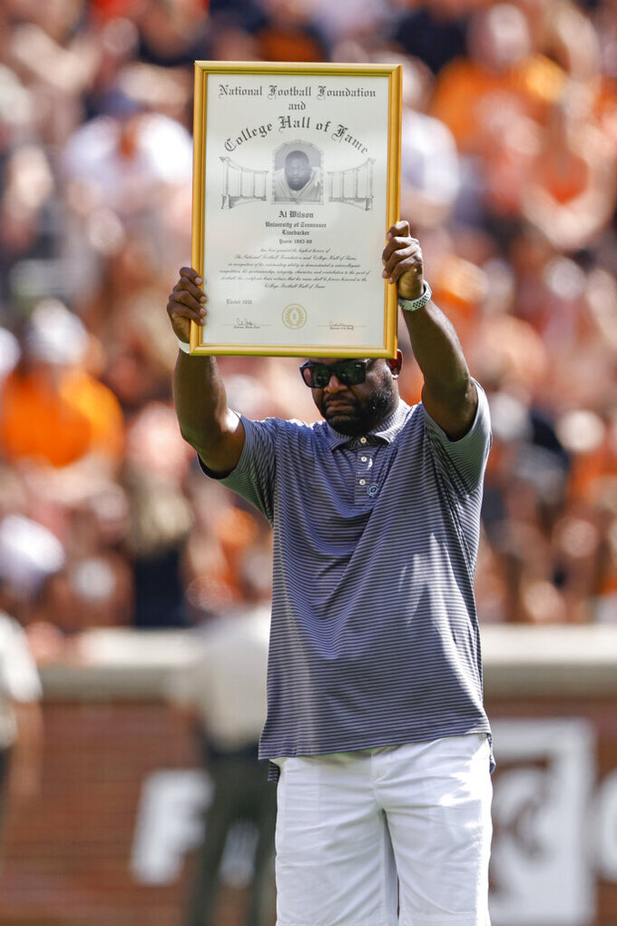 Former Tennessee linebacker Al Wilson holds up a plaque as his induction into the National Football Foundation and College Hall fo Fame is announced during halftime of an NCAA college football game against South Carolina Saturday, Oct. 9, 2021, in Knoxville, Tenn. (AP Photo/Wade Payne)