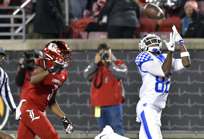 Kentucky wide receiver Josh Ali (82) reaches for a pass ahead of the defense of Louisville cornerback Cornelius Sturghill (3) during the second half of an NCAA college football game in Louisville, Ky., Saturday, Nov. 24, 2018. Kentucky won 56-10. (AP Photo/Timothy D. Easley)