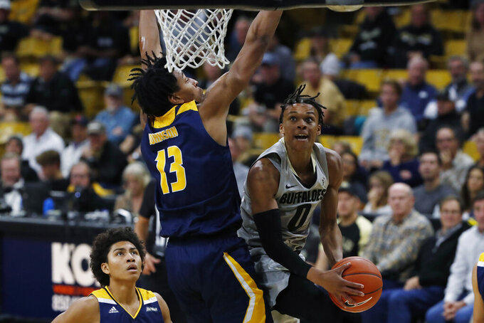 Colorado guard Shane Gatling, right, goes up for a basket as UC Irvine forward Austin Johnson defends in the second half of an NCAA college basketball game Monday, Nov. 18, 2019, in Boulder, Colo. (AP Photo/David Zalubowski)
