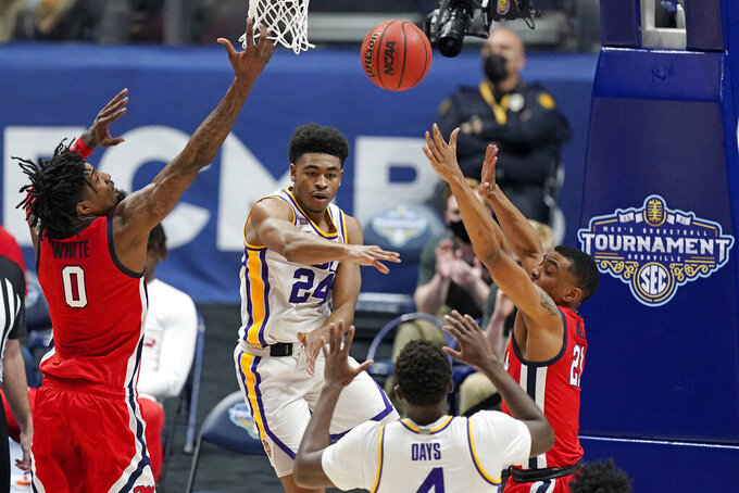 LSU's Cameron Thomas (24) passes the ball past the reach of Mississippi's Romello White (0) and Robert Allen (21) in the first half of an NCAA college basketball game in the Southeastern Conference Tournament Friday, March 12, 2021, in Nashville, Tenn. (AP Photo/Mark Humphrey)