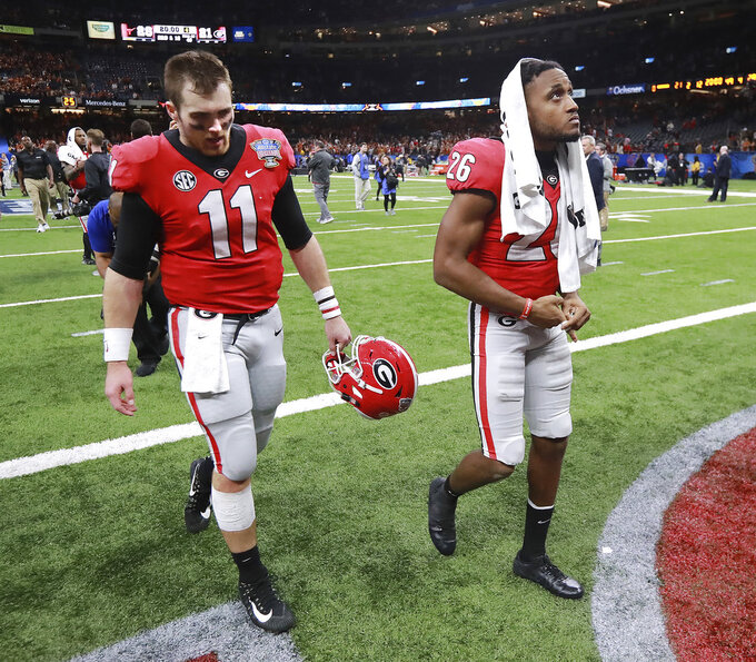Georgia quarterback Jake Fromm and defensive back Tyrique McGhee walk off the field after the team's 28-21 loss to Texas in the Sugar Bowl NCAA college football game Tuesday, Jan. 1, 2019, in New Orleans. (Curtis Compton/Atlanta Journal Constitution via AP)