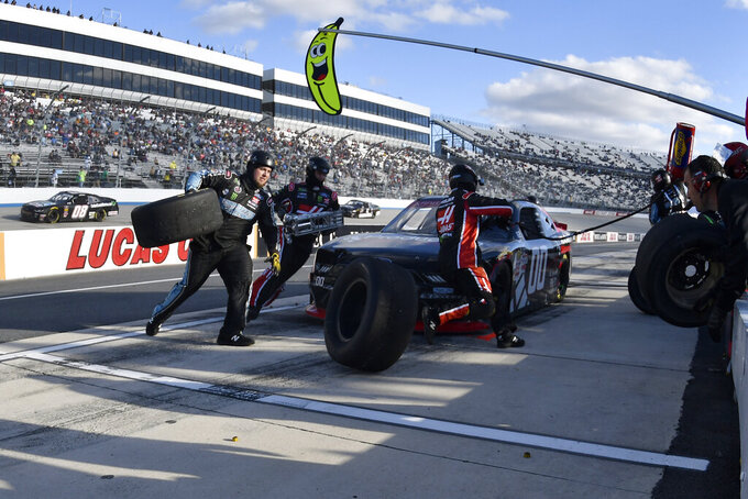 The team of driver Cole Custer car performs a pit stop late in the race during the  NASCAR Xfinity Series auto race, Saturday, Oct. 5, 2019, in Dover, Del. (AP Photo/Brien Aho)