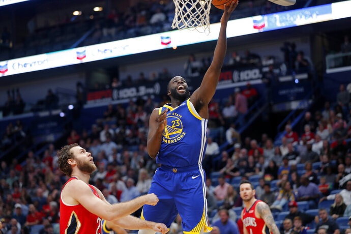 Golden State Warriors forward Draymond Green (23) goes to the basket over New Orleans Pelicans forward Nicolo Melli, left, in the first half of an NBA basketball game in New Orleans, Monday, Oct. 28, 2019. (AP Photo/Gerald Herbert)