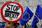 Anti-Brexit demonstrators wave banners and flags outside the Cabinet Office in London, Friday, Aug. 30, 2019. A legal challenge aimed at stopping Boris Johnson's suspension of Parliament has been denied an interim interdict at the Court of Session in Edinburgh on Friday. A cross-party group of MPs and peers filed a petition at Scotland's highest civil court earlier this summer aiming to stop the Prime Minister being able to prorogue Parliament. (AP Photo/Kirsty Wigglesworth)