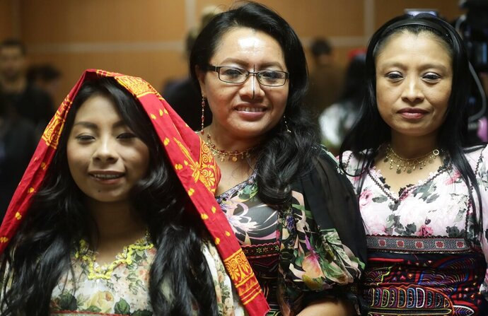 Guna indigenous women pose for a photo wearing traditional dresses decorated with Molas, after a press conference where Guna leaders demanded that the sports shoe company Nike remove their traditional Mola handcraft print from a shoe design, in Panama City, Tuesday, May 21, 2019. Nike said in a statement that it has canceled the launch of the