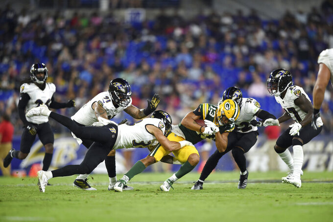 Green Bay Packers wide receiver Allen Lazard (13) is tackled by Baltimore Ravens defensive back Bennett Jackson, center left, and a host of Ravens defenders during the second half of an NFL football preseason game, Thursday, Aug. 15, 2019, in Baltimore. (AP Photo/Gail Burton)