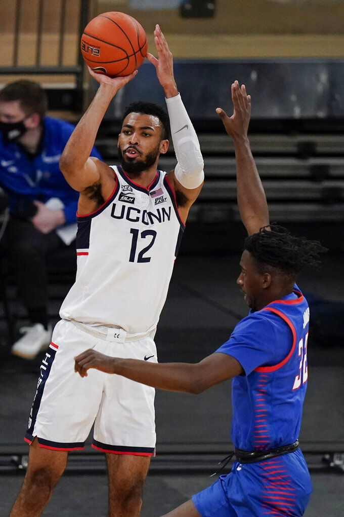 Connecticut's Tyler Polley (12) shoots next to DePaul's David Jones (32) during the second half of an NCAA college basketball game in the Big East conference tournament Thursday, March 11, 2021, in New York. (AP Photo/Frank Franklin II)