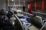 A man takes a nap as investors monitor stock prices at a brokerage house in Beijing, Friday, Dec. 6, 2019. Shares swung higher in Asia on Friday after a wobbly day of trading on Wall Street as investors awaited a U.S. government jobs report and kept an eye out for developments in China-U.S. trade talks. (AP Photo/Andy Wong)