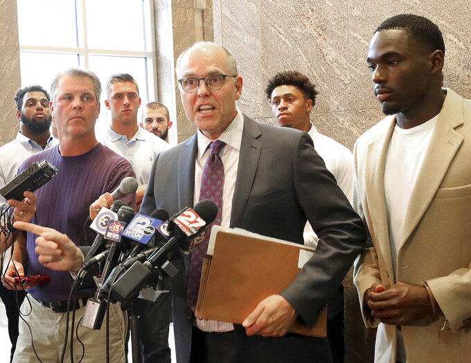 Stephen Meyer, center, attorney for former Wisconsin Badger football player Quintez Cephus, right, speaks on behalf of his client during a press conference in Madison, Wis. Monday, Aug. 12, 2019. Cephus, who was acquitted of sexual assault charges earlier this month, is requesting to be reinstated to the university which expelled him after completing their own investigation in March. (John Hart/Wisconsin State Journal via AP)