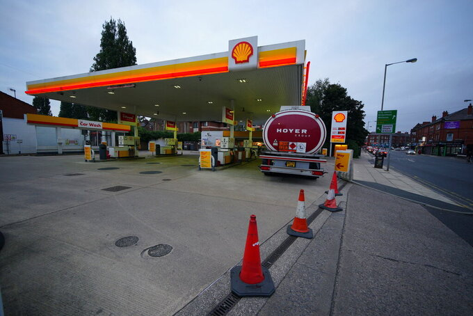 A petrol tanker delivers fuel to a petrol station in Liverpool, England,  Thursday Sept. 23, 2021, which was closed due to having no fuel. The British government is trying to ease concerns of a fuel crisis after oil giants BP and ExxonMobil-owned Esso warned they had to ration supplies and close some gas stations as a result of a truck driver shortage. (Peter Byrne/PA via AP)