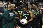 FILE - In this Jan. 17, 2020, file photo, former Michigan State guard Mateen Cleaves, left, presents guard Cassius Winston with a commemorative basketball after Winston broke Cleaves all time Big Ten and Michigan State records, after an NCAA college basketball game against Wisconsin in East Lansing, Mich. Winston was selected to the Associated Press All-Big Ten team selected Tuesday, March 10, 2020. (AP Photo/Carlos Osorio, File)