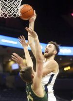 Virginia forward Jay Huff (30) shoots over William & Mary forward Ben Wight (35) during an NCAA college basketball  game Tuesday, Dec. 22, 2020, in Charlottesville, Va. (Andrew Shurtleff/The Daily Progress via AP)
