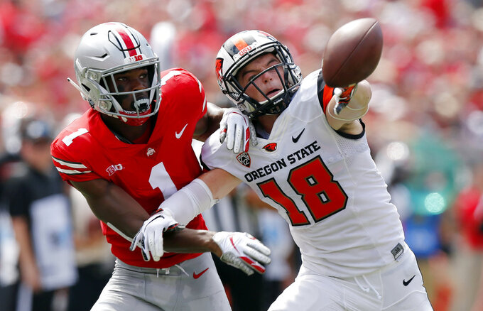 Ohio State defensive back Jeffrey Okudah, left, knocks the ball away from Oregon State wide receiver Timmy Hernandez during the first half of an NCAA college football game Saturday, Sept. 1, 2018, in Columbus, Ohio. (AP Photo/Jay LaPrete)