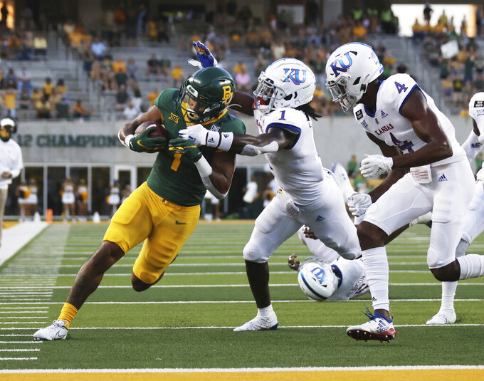 Baylor running back Trestan Ebner, left, gets close to the goal line before getting pulled down by Kansas cornerback Kenny Logan Jr., in the first half of an NCAA college football game, Saturday, Sept. 26, 2020, in Waco, Texas. (Rod Aydelotte/Waco Tribune-Herald via AP)