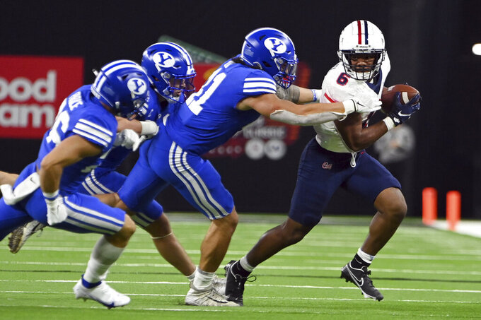 Arizona running back Michael Wiley (6) runs with the ball under pressure from BYU during the second half of an NCAA college football game Saturday, Sept. 4, 2021, in Las Vegas. (AP Photo/David Becker)