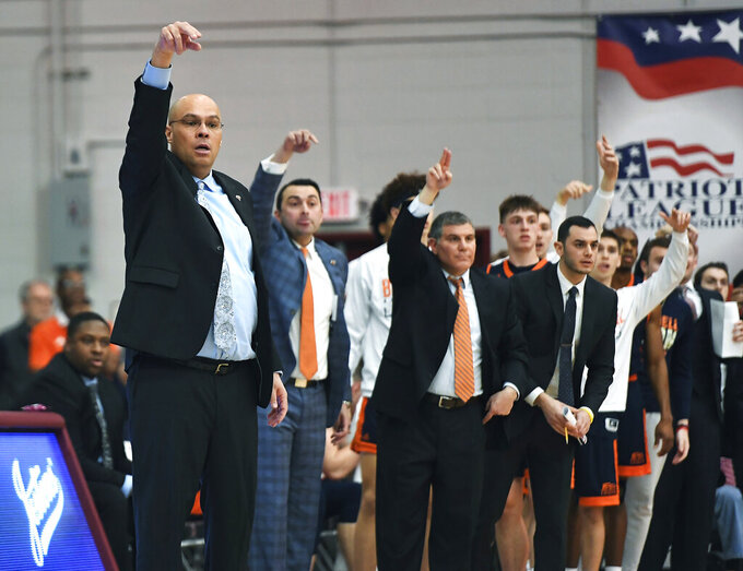 Bucknell coach Nathan Davis, left, and his bench signal for a call from the referee during the first half of an NCAA college basketball game against Colgate for the championship of the Patriot League men's tournament in Hamilton, N.Y., Wednesday, March 13, 2019. (AP Photo/Adrian Kraus)