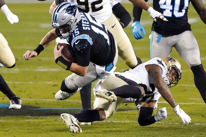 Carolina Panthers' Tommy Stevens is tackled by New Orleans Saints cornerback P.J. Williams during the second half of an NFL football game Sunday, Jan. 3, 2021, in Charlotte, N.C. (AP Photo/Brian Blanco)