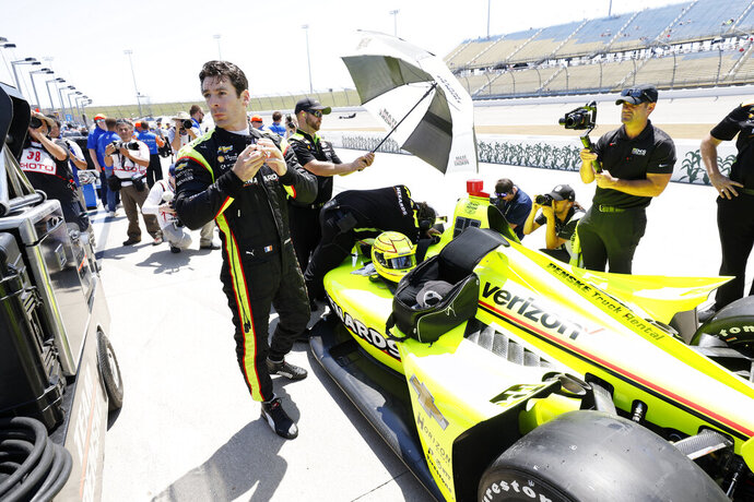 Simon Pagenaud stands next to his car during qualifying for the IndyCar Series auto race Friday, July 19, 2019, at Iowa Speedway in Newton, Iowa. (AP Photo/Charlie Neibergall)