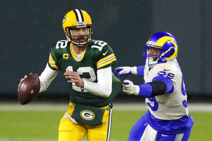 Green Bay Packers quarterback Aaron Rodgers (12) throws under pressure from Los Angeles Rams' Aaron Donald (99) during the first half of an NFL divisional playoff football game Saturday, Jan. 16, 2021, in Green Bay, Wis. (AP Photo/Matt Ludtke)