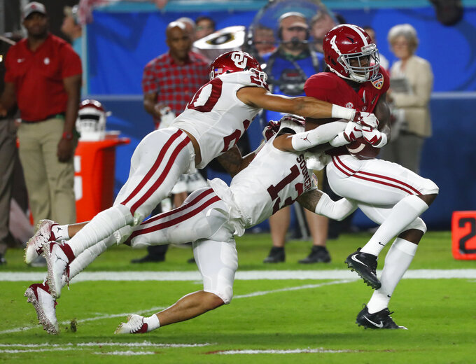 Oklahoma safety Robert Barnes (20) and cornerback Tre Norwood (13) tackle Alabama wide receiver Jerry Jeudy (4), during the first half of the Orange Bowl NCAA college football game, Saturday, Dec. 29, 2018, in Miami Gardens, Fla. (AP Photo/Wilfredo Lee)