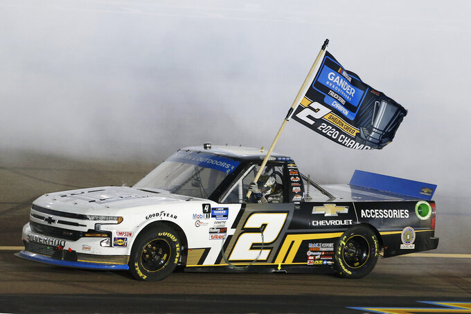 Sheldon Creed drives through the smoke from his burnout while holding a season champion banner after winning the NASCAR Truck Series auto race at Phoenix Raceway, Friday, Nov. 6, 2020, in Avondale, Ariz. (AP Photo/Ralph Freso)
