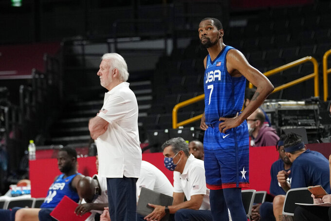 United States coach Gregg Popovich, left, and forward Kevin Durant (7) look on from the side line during their loss to France in a men's basketball preliminary round game at the 2020 Summer Olympics, Sunday, July 25, 2021, in Saitama, Japan. (AP Photo/Eric Gay)