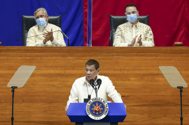 In this handout photo provided by the Malacanang Presidential Photographers Division, Philippine President Rodrigo Duterte, center, delivers his State of the Nation Address (SONA) while Senate President Vicente Sotto III, left, and House Speaker Alan Peter Cayetano applauds at the House of Representative in Metro Manila, Philippines, Monday, July 27, 2020. (Simeon Celi Jr./Malacanang Presidential Photographers Division via AP)