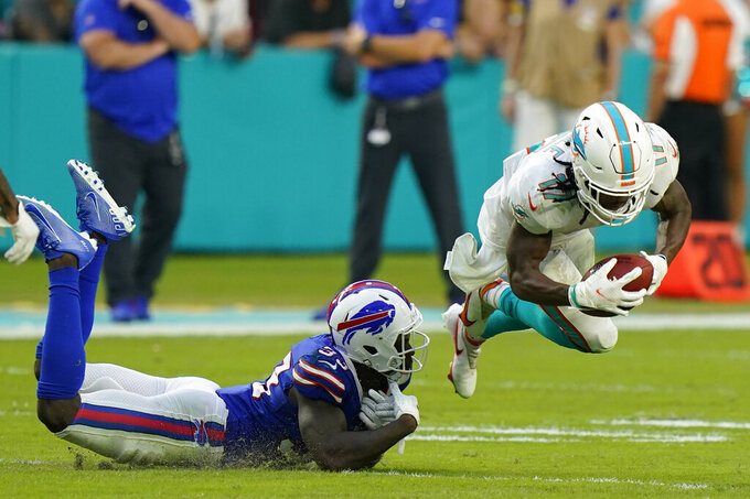 Miami Dolphins wide receiver Jaylen Waddle (17) goes flying as Buffalo Bills defensive back Siran Neal (33) attempts a tackle, during the second half of an NFL football game, Sunday, Sept. 19, 2021, in Miami Gardens, Fla. (AP Photo/Wilfredo Lee)