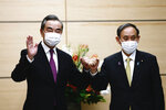 Japan's Prime Minister Yoshihide Suga, right, bumps fists with China's Foreign Minister Wang Yi at the start of their meeting in Tokyo, Wednesday, Nov. 25, 2020. (Behrouz Mehri/Pool Photo via AP)