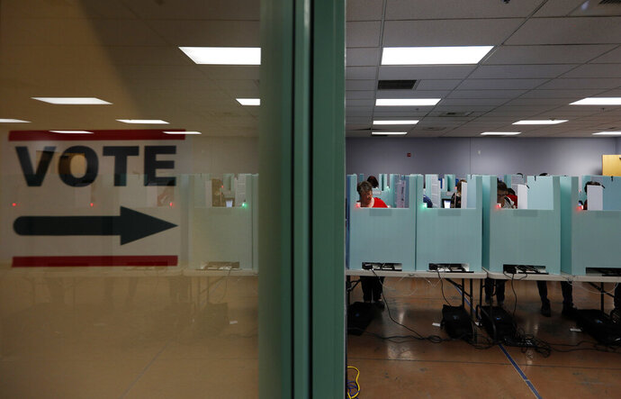 FILE - In this Nov. 6, 2018, file photo, people vote at a polling place in Las Vegas. Nevada, the third state to vote on the presidential primary next year, is supposed to offer Democrats something different. It's more diverse than largely white Iowa and New Hampshire. Its population is working class, urbanized and increasingly blue. (AP Photo/John Locher, File)