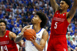 Kentucky's Nick Richards, middle, shoots between Louisville's Dwayne Sutton (24) and Malik Williams (5) during the first half of an NCAA college basketball game in Lexington, Ky., Saturday, Dec. 28, 2019. (AP Photo/James Crisp)