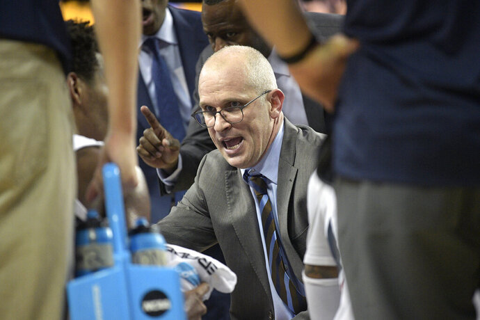 FILE - In this Thursday, Jan. 31, 2019 file photo, Connecticut head coach Dan Hurley, center, talks to his players during a timeout in the second half of an NCAA basketball game against Central Florida in Orlando, Fla. UConn men's basketball coach Dan Hurley is back at work full time, less than two weeks after having surgery for a degenerative spinal condition that required replacing two disks in his neck with artificial ones. On Wednesday, Sept. 18, 2019 Hurley described the fear he felt when doctors told him in August that he needed surgery and that any hard fall or bump could have left him paralyzed.  (AP Photo/Phelan M. Ebenhack, File)